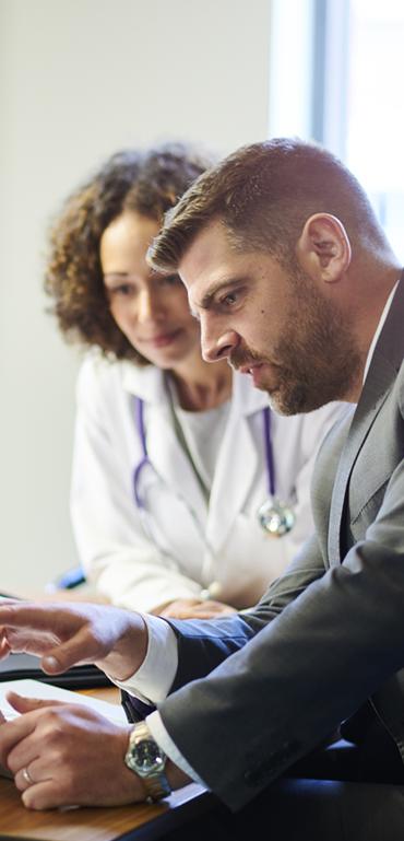 A man in a suit and a woman in a doctor's coat are looking at a computer monitor.