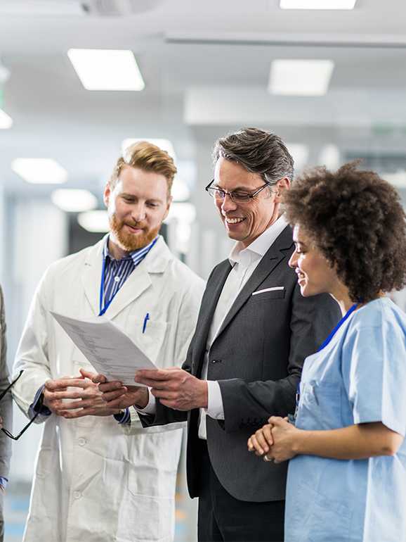 A doctor and a nurse stand on either side of a person in a suit. They are all looking over a document and smiling.